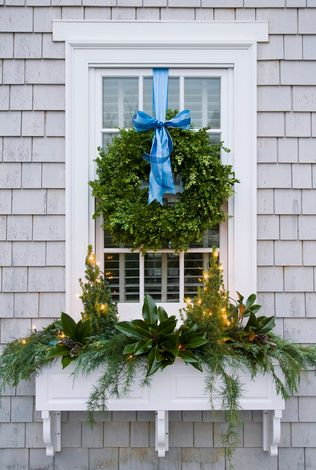 This decorated window box with a variety of fresh greenery and boxwood wreath gives a complete look for the exterior of this home!