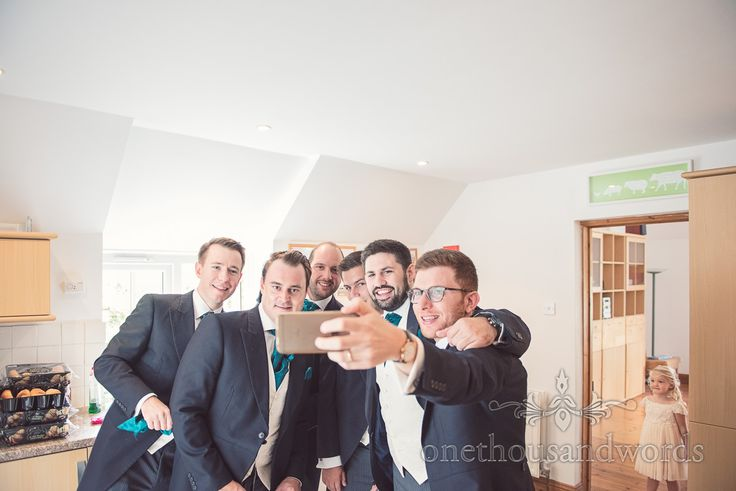 Groomsmen in green cravats take wedding morning selfie watched by flower girl. Photography by one thousand words wedding photographers
