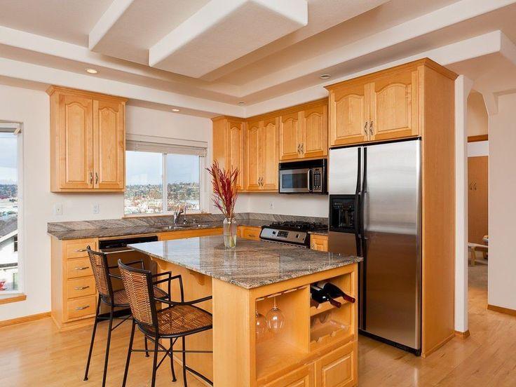 Ein Licht getönten Holz Kücheninsel mit grau Keramik-Arbeitsplatte steht in der Mitte dieses offene Konzept L-förmige Küche.