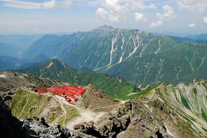 槍ヶ岳の頂上で、槍ヶ岳山荘と笠ヶ岳を眺める。何人もの登山者がしてきた儀式。