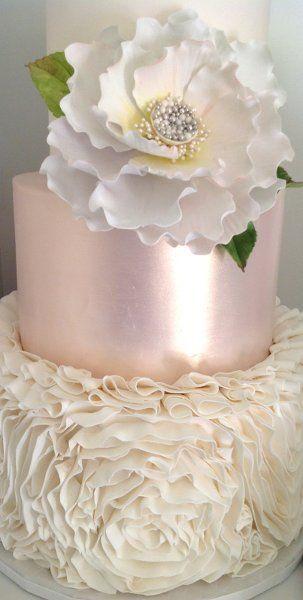 Pink metallic wedding cake with sugar flowers.