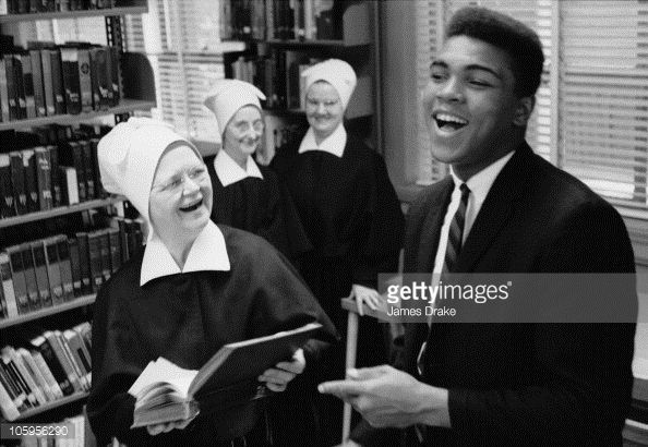 American boxer Muhammad Ali shares a laugh with members of the Congregation of the Sisters of Charity of Nazareth in the library of Nazareth College...