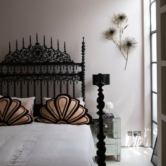Modern bedroom with gothic bed  Bring antiques bang up-to-date by teaming with contemporary furniture. Here an antique bed takes pride of place in this bedroom, while mirrored furniture adds a touch of modern style.  Similar antique bed Guinevere