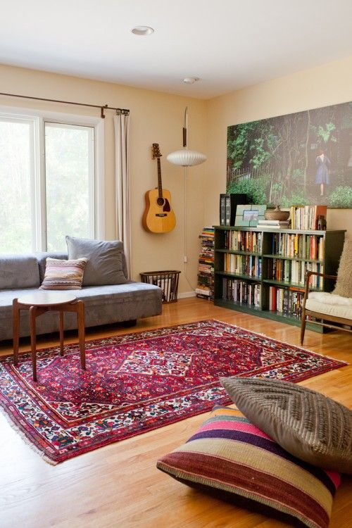 Wooden floor, bright persian-style rug and colourful cushions in Carrie Olshan's LA home via Design Sponge