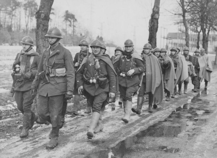 A Group Of French Soldiers Walking Along The Road On The