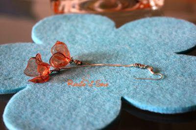 """Orecchini lunghi 9 cm in plastica arancione!  Composti da due """"catenelle"""", in metallo argentato, che terminano con due piccoli fiorellini a campanula. #orecchini #plastica #riciclo"""