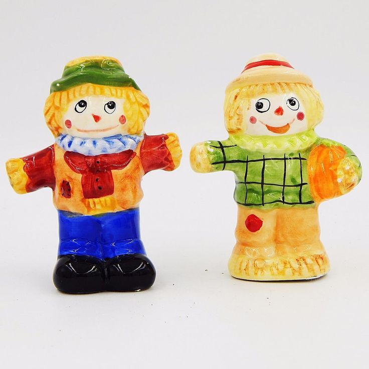 Pre-owned collectible gloss glazed porcelain ceramic figural novelty salt and pepper shakers set. Two piece set features a pair of fall, autumn or Thanksgiving scarecrows.  One scarecrow is wearing a scarf, brown shirt, blue pants, black shoes and hat with green brim.  The other scarecrow has a green shirt, tan pants, hat with red band and is holding an orange pumpkin under one arm. #SaltAndPepperShakers #Scarecrow #Thanksgiving