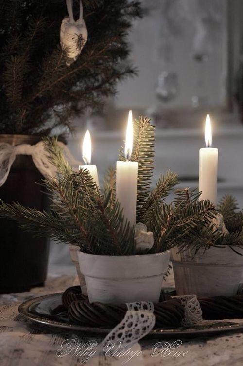 Minimalistische und zugleich wunderschöne Weihnachtsdeko. Weiße Tontöpfe mit Tannenzweigen und weißen Stabkerzen.
