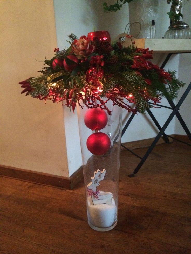 Mooi rood kerststuk in hoge glazen vaas
