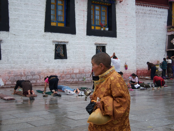 Monk and praying people outside a religious place in Thibet.