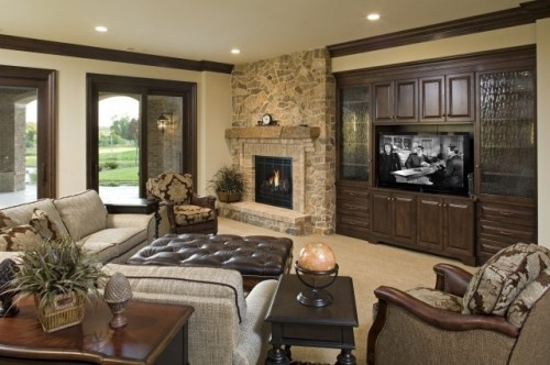 Stone floor to ceiling fireplace balances nicely done wood built-in for TV . Comfortable room with good light and inviting furniture.