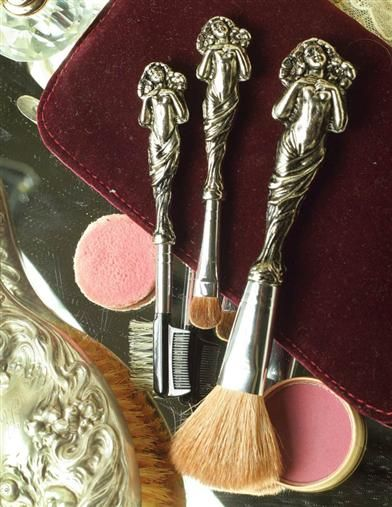 Love Disarmed Cosmetic Brushes - An art nouveau beauty strikes a modest pose atop vanity essentials. Victorian style silver-plated makeup brushes in velvet carrying pouch.