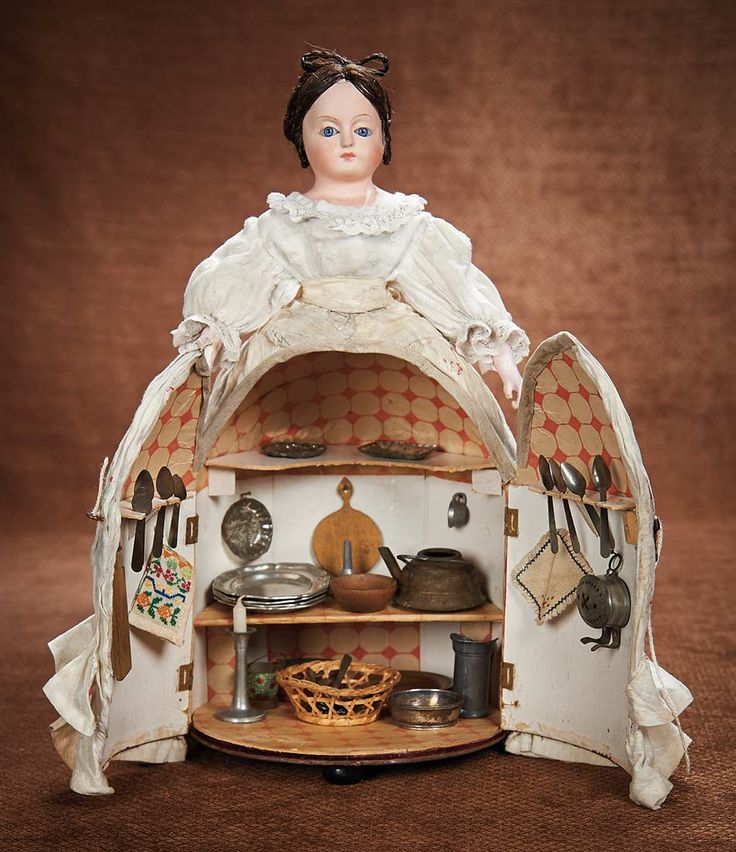 Very rare, all original German papier-mâché novelty doll with blue glass eyes, slit-inserted brunette hair in elaborate coiffure, with cone-shaped skirt that opens at center front to reveal a miniature kitchen with lithographed paper tile walls and floors, and fitted with shelves, a table, and an abundance of tinware plates, pots, and utensils. Circa 1870.