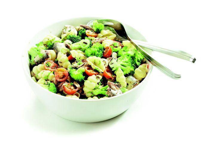 Giet de olie van de sardientjes boven een slakom af en vermeng dit met het citroensap. Verwijder de graten uit de sardientjes en schep ze in de slakom, met peterselie en knoflook. Kook de macaroni beetgaar en voeg de laatste 2 à 3 minuten de broccoliroosjes toe. Schep de cherrytomaten en lente-ui bij de sardientjes. Giet de pasta met broccoli af en schep het mengsel direct, dus warm, door de ingrediënten in de kom. Schep alles luchtig om. Serveer het gerecht lauwwarm.