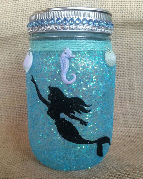 This beautiful light is made with a pint size mason jar covered in 2 layers of glitter and sealed to prevent the glitter from falling off. A mermaid silhouette is added to create a gorgeous light perfect for any room or even for an outdoor event. This jar is made to order so the charms and twine may differ from the ones shown in the listing. I always make the jars as close to the listing pictured as I can.These jars use coin batteries. I do not recommend leaving this light on all night since…