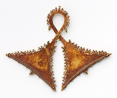 Indonesia ~ south Moluccas  | Pectoral in double axe head form [taka] from the Babar Islands | 19th century | Gold alloy, cinnabar | Heirloom treasures are essential to ritual and communication with the ancestors. Across eastern Indonesia gold pectorals are created in the arresting double-axe form. Among these are the delicate taka pendants from Flores.