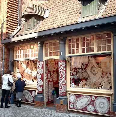 Bruges Lace Shop Women in traditional costumes and coke bottle eye glasses sit on the sidewalk making bobbin lace.