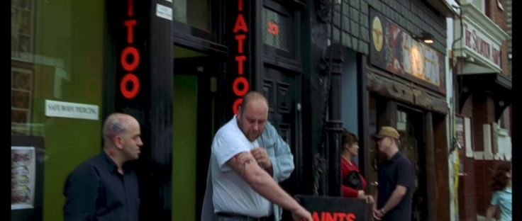 Will (Hugh Grant) is passing by the Saints Tattoo Parlour on his way to the bookstore.   #nottinghill #movie #scene