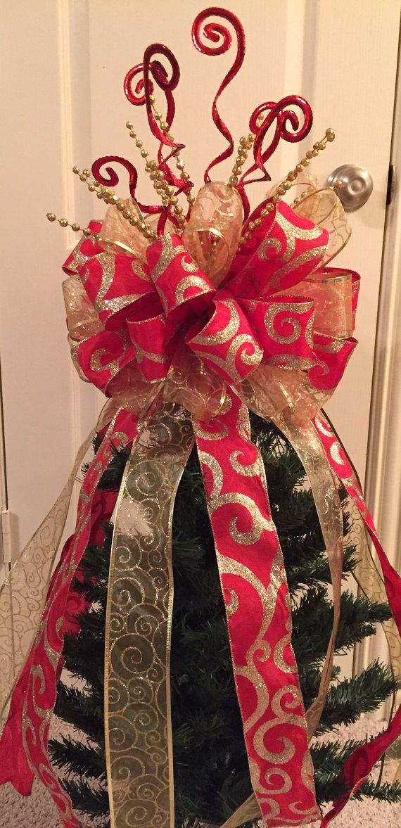 Large Christmas Tree Bow Topper - Red & Gold Made with 2.5 wired ribbon and decorative picks. Contains 32 loops of ribbon and 6 -2ft. long streamers. Attached to a large pick to poke down into the top of your tree to stabilize. Ribbons contain glitter to catch the light and sparkle.