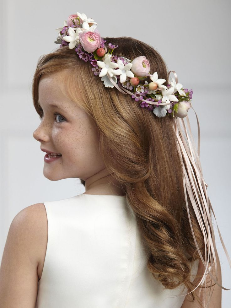 This beautiful head dress will make any flower girl glow. Pink ranunculus, white stephanotis blooms, pink waxflower, peach hypericum berries and dusty miller stems are arranged in the perfect circle and accented with peach satin ribbon to crown her head on the wedding day, giving your flower girl a sweet look for her big moment.