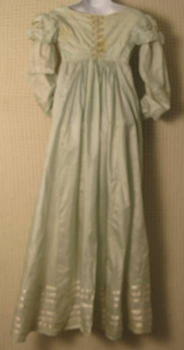 """Andrew H. Green Estate and Antiques Auction - Worcester, Massachusetts - U.S.A.  Lot 73. Regency Period China Silk Gown Circa 1805 Palest blue China silk gown. Lined sleeves with diamond cut out shoulder puffs trimmed in ivory """"pinked"""" satin ribbon. Back closures are ivory silk corded loops that hook on fine silk thread wrapped buttons. Condition: Fabric is whole without rips or tears. Staining on front of gown and some light fading. Owner attribution based on date/style to Lydia Pinkham…"""