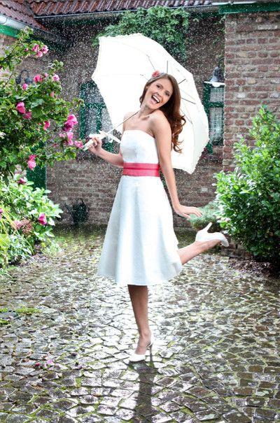 kurzes brautkleid mit schwingendem glockenrock (http://www.noni-mode.de) bride with short cut strapless wedding dress with decorative waistband in pink, dancing in the rain with an umbrella.
