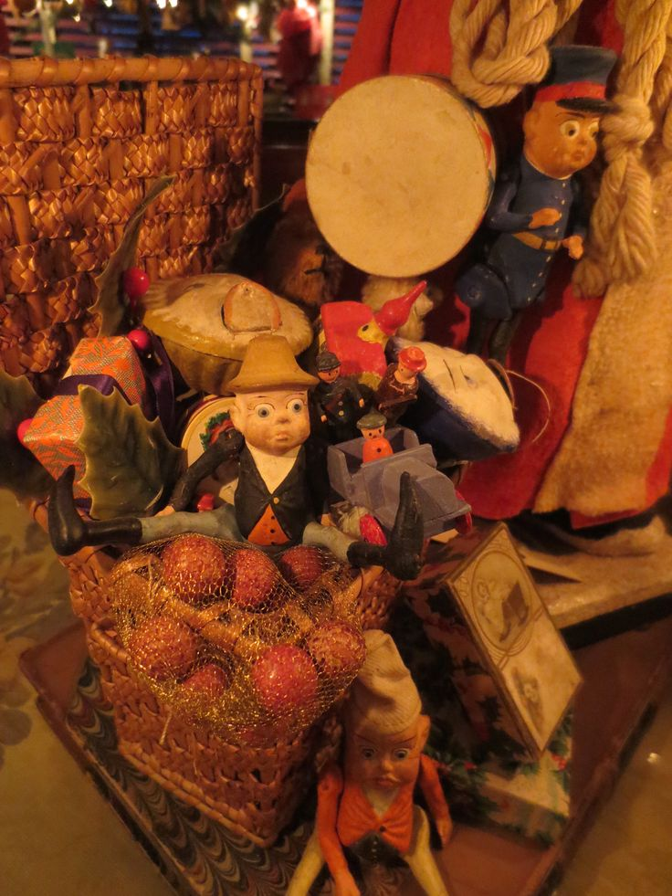 A Basket Of German Toys Including Palmer Cox Composition Brownies Sit Next To The