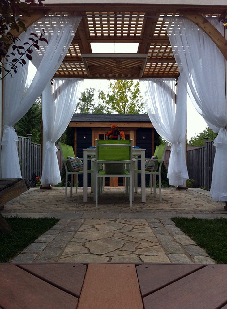 """This project features a stone dining area sheltered by an elegant pergola, with breezy curtains offering shade and privacy, with an attractive shed for storage.  Built on """"Decked Out"""" episode """"The Deck That's Narrow"""".  Deck Design by Paul Lafrance Design."""