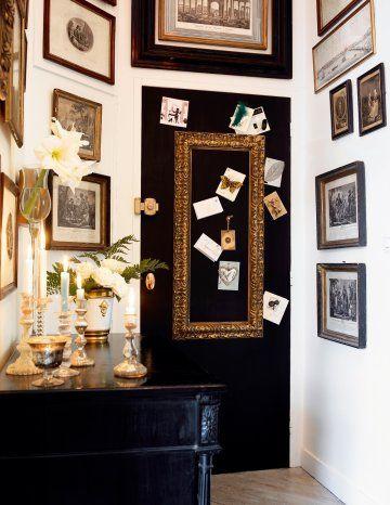 Porte d'entrée peinte en noire, décorée d'un cadre doré et de cartes de vœux accrochées avec des aimants