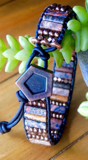 Designed and handmade in North Carolina, USA by myself. LEOPARDSKIN JASPER & Antique Copper on Black Leather  a unisex Leather single bracelet featuring Leopardskin Jasper (both the square and round column beads) and antiques copper faceted metal beads and Japanese glass beads.. All sewn with Tuff Cord Nylon Beading Cord for great durability . Black ecofriendly greek Leather and a Hexagon antique copper Button providing 3 closure options measuring 8, 9.25 and 10.57.75, 9 and 10 . The…