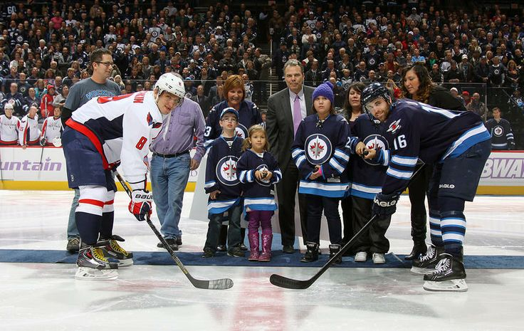 Alex Ovechkin and Andrew Ladd take the ceremonial face-off following a cheque presentation on behalf of the Winnipeg Jets organization to CancerCare Manitoba in honor of #HockeyFightsCancer night at the MTS Centre on October 22, 2013 in Winnipeg.