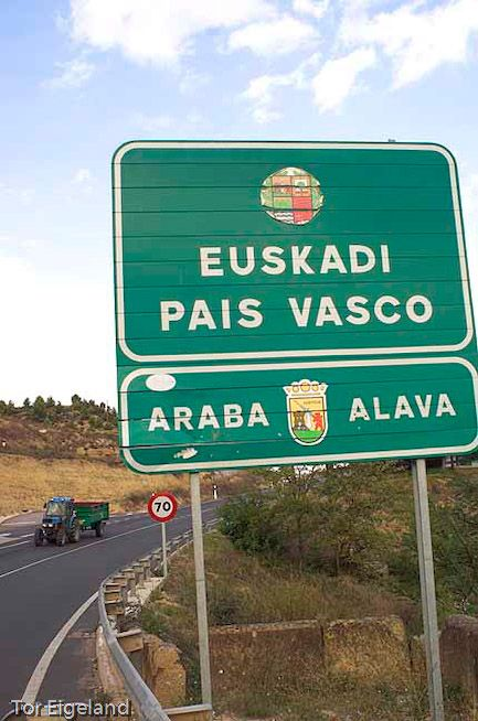 Spain. Basque Country. Sign marking entrance into Basque Country, Alava district. Tractor loaded with grapes.