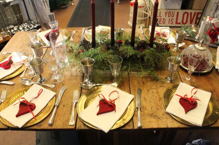 Julbordet dukat med mässing, tenn, glas, linneservetter och trähjärtan.