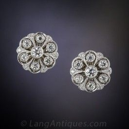 These classic and enchanting vintage-style diamond stud earrings are beautifully crafted to emulate early-twentieth century Edwardian period originals, which are nearly impossible to find. Featuring a floral cluster of bright-white European-cut diamonds set in finely milgrained platinum and backed with 18 karat yellow gold, these wonderful and wearable earrings measure just shy of 1/2 an inch in diameter.