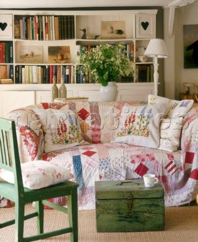 A country sitting room  upholstered sofa with patchwork cover  wooden chest  painted chair  shelving