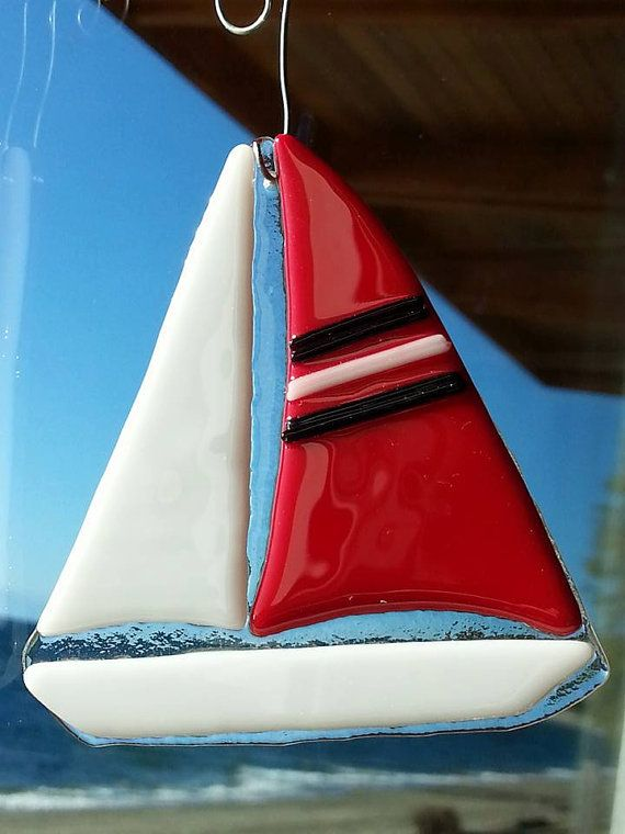 Hand cut, kiln fused sailboat Christmas tree ornament. Red sail with blue and white stripes.  Measures 3 1/4 X 3 1/4, excluding hanger.  Comes