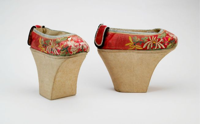 """Bata Shoe Museum:  Manchu platforms19th centuryChinaThe Bata Shoe Museum. Manchu women were forbidden by law to have their feet bound, as was the custom among Han Chinese women. In order to mimic the desirable """"lotus gait"""" of the Han women, Manchu women added high platforms to their shoes that stilted their gait. This pair is beautifully embroidered with a peony motif."""