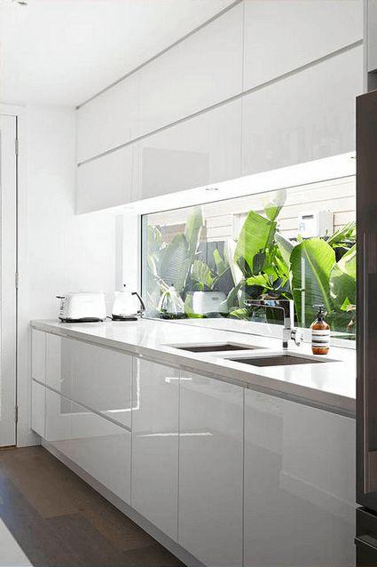 Cozinha decorada, piso amadeirado escuro, armários brancos, bancada branca e backsplash/janela com vidro inteiro. Lindas ideias de Backsplash de vidro na Cozinha