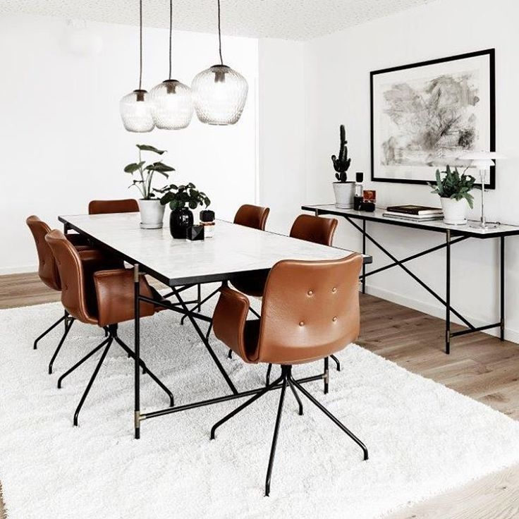 Primum dining chairs in cognac leather around a marble dining table.