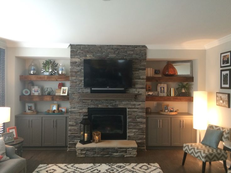 Our beautiful reclaimed wood floating shelves. Flanking stone fireplace with grey base cabinets located in family room.