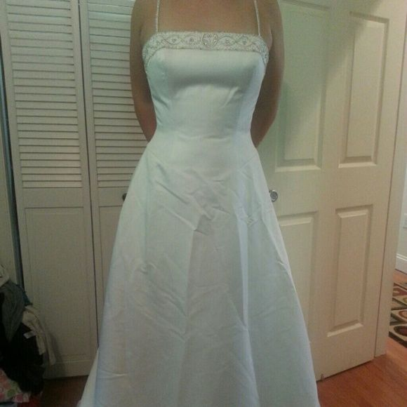 ANJOLIQUE WEDDING DRESS New Strapless or diamond strapped white wedding dress. Very pretty. Silver threaded embroidered neckline and train. SIZE 14. This dress has not been worn, but has been in storage for a few years. It will need two be aired out, dry cleaned and steamed. Has original tag from bridal salon $770. Anjolique Dresses