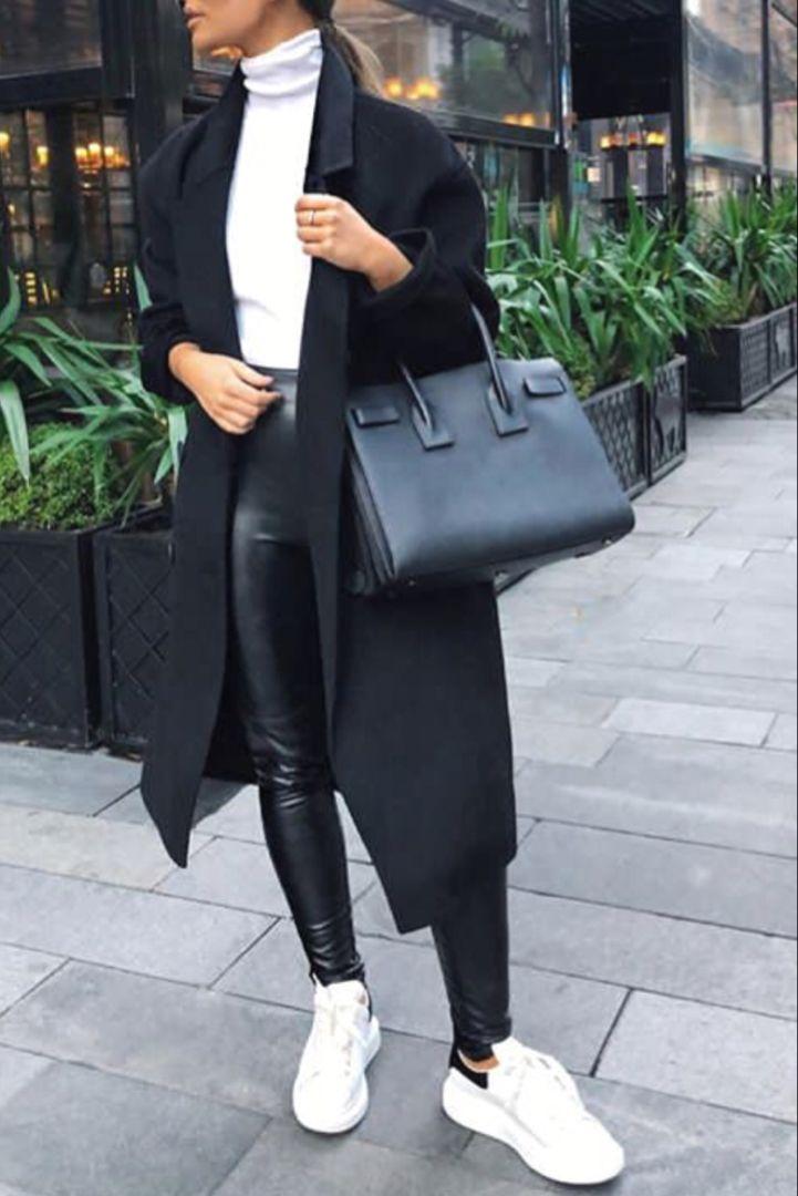 Mode Frau Herbst / Winter mit einem langen schwarzen Mantel, weißen Turnschuhen, einem Pullover