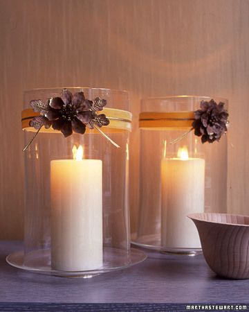 Fall flowers and paper leaves accessorize hurricane vases