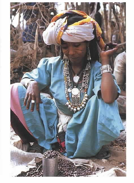 Africa | An Oromo woman. Trading with the Afar at Senbete market, Eritrea.  Oromo women are noted for their colourful headcloths and beautifully crafted silver jewellery made from Austrian Maria Theresa dollars, which were used as a trading currency in Ethiopia for many years. | ©Carol Beckwith and Angeloa Fisher ~ African Ark: Peoples of the Horn. 1990