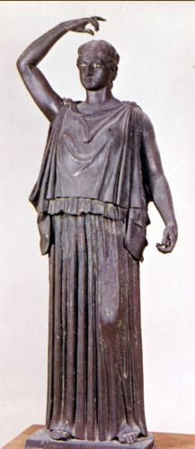 Here is a picture of what a Doric Chiton looked like in Ancient Greece.  This picture is very similar to the modern day dress on the red carpet, showing both of the sides being pinned right on top of the shoulders, with some ruffles in the middle along with a small fabric belt with material covering it to form what looks like layers.  Doric Chitons are sleeveless garments as this image here shows.