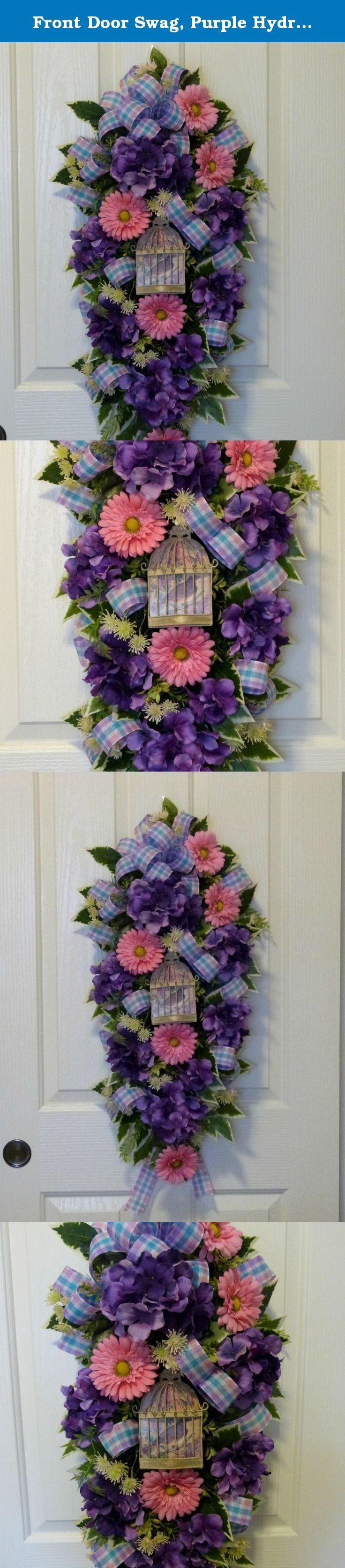 Front Door Swag, Purple Hydrangea Swag, Spring Door Swag With Hydrangeas. Welcome your guests with this gorgeous purple hydrangea door swag on your front door. This swag was made on a pine base with beautiful lush greenery including variegated ficus, boxwood, and asparagus fern. Flowers include Vibrant purple hydrangeas and pink gerbera daisies. A metal sign with pretty bird is in the center. Large pink, lavender, blue plaid bow is on the top with loops added throughout the swag. Silk...