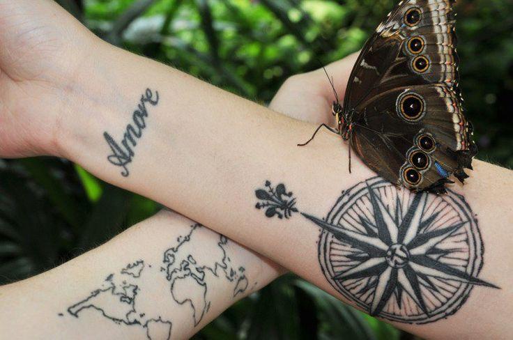 tatouage rose des vents avec fleur-de-lis indiquant le Nord et carte mondiale sur l'autre bras