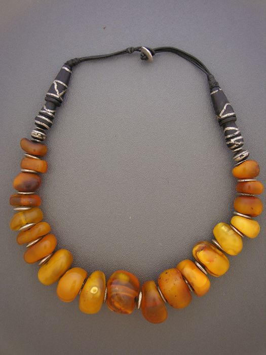 by Anna Holland   Antique Moroccan fossil amber, with silver discs and antique Mauritanian imam beads (from a strand of prayer beads). The imam beads have inlaid silver wire in the surface of the ebony wood.   3,495$