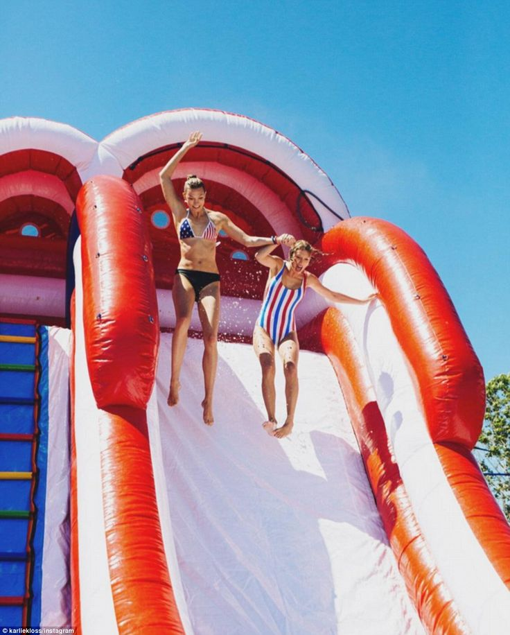 Jumping for joy! Taylor Swift zipped hand-in-hand down a giant, inflatable water slide wit...