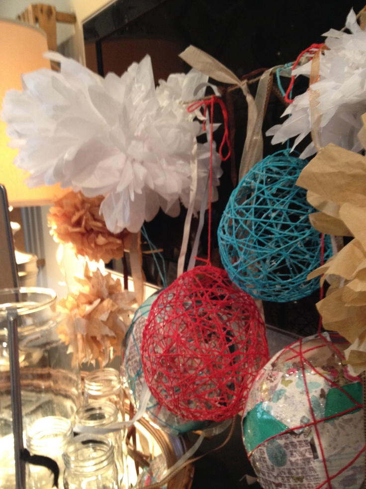 tissue pon pons, yarn balls, and scrap booking paper clustered together to make a fun backdrop